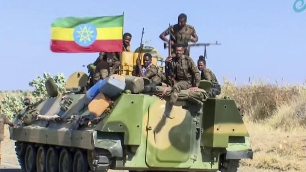 Ethiopian military sitting on an armored personnel carrier next to a national flag, in an area near the border of the Tigray and Amhara regions of Ethiopia.(AP)