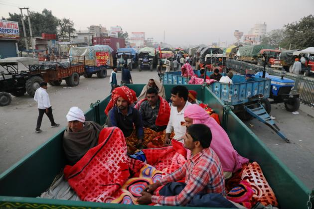 Farmers rest inside a trailer at a site of a protest against the newly passed farm bills at Singhu border near Delhi.(REUTERS)