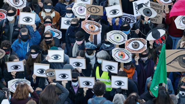 Demonstrators hold placards as they gather at the Place de la Republique square in Paris on November 28. Tens of thousands took to the streets to protest against new security legislation that would criminalise the publication of images of on-duty police officers with the intent of harming their physical or psychological integrity, AFP reported. (Thomas Coex / AFP)