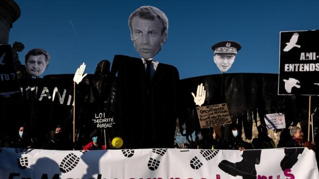 "Demonstrators hold effigies of French President Emmanuel Macron, French Interior Minister Gerald Darmanin and Paris police prefect Didier Lallement at the Place de la Republique in Paris on November 28. Macron said on November 27 that the images of the beating of black music producer Michel Zecler by police officers in Paris ""shame us."" The incident had magnified concerns about alleged systemic racism in the police force, AFP reported. (Joel Saget / AFP)"
