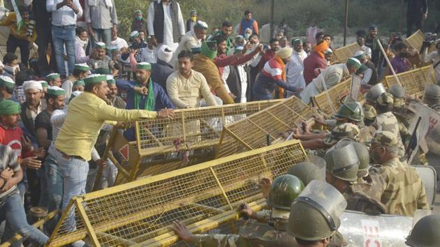 Police personnel reinforce barricades as Bharatiya Kisan Union (BKU) members attempt to break past them at the Delhi-UP Gate border in Ghaziabad on Sunday. (Photo by Sakib Ali /Hindustan Times)
