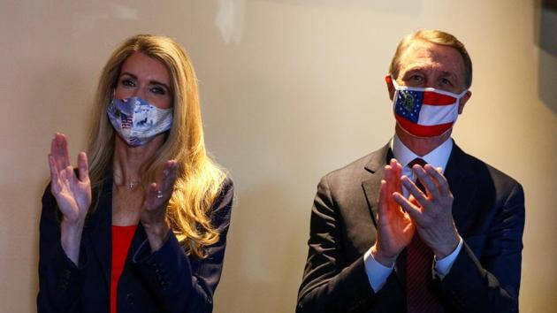 US Senators David Perdue and Kelly Loeffler wearing protective masks clap during a campaign event in Cumming, Georgia, US.(Reuters)