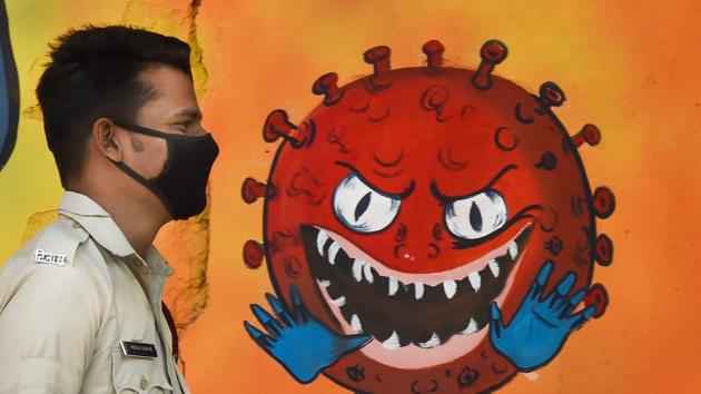 A DCD volunteer wearing face mask walks past a mural on novel coronavirus and protective measures, in New Delhi, on November 24.(PTI File Photo)