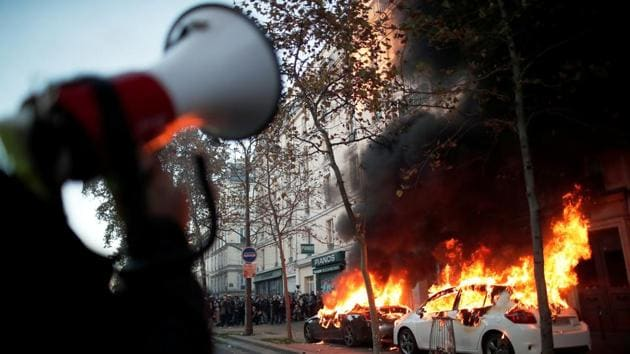 A police officer speaks on a loudspeaker as a car is set on fire by demonstrators in Paris on November 28. An investigation has been opened against the four police personnel involved in the beating of the Black music producer but commentators say that the images -- first published by the Loopsider news site -- may never have been made public if the contentious Article 24 of the security legislation was made law, AFP reported. (Benoit Tessier / REUTERS)