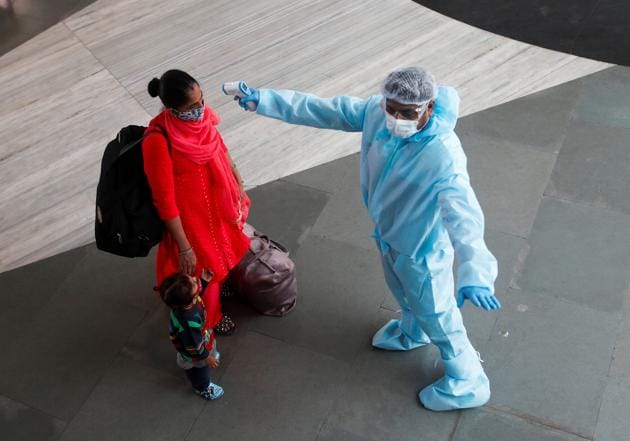 A health worker in personal protective equipment (PPE) checks the temperature of a passenger at a railway station, amid the spread of the coronavirus disease (COVID-19), in Mumbai, on November 27.(REUTERS)