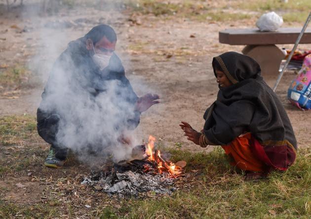 People near a bonfire in New Delhi on Sunday.(PTI)