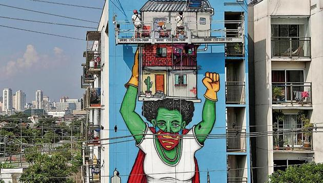 Artist Mundano works on a graffiti called Invisible Heroines, a tribute to women braving pandemic in Sao Paulo, Brazil.