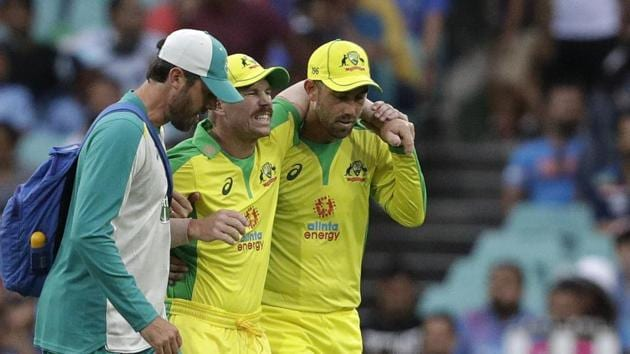 Australia's David Warner, centre, is assisted from the field after injuring himself while fielding during the one day international cricket match between India and Australia at the Sydney Cricket Ground in Sydney, Australia, Sunday, Nov. 29, 2020. (AP Photo/Rick Rycroft)(AP)