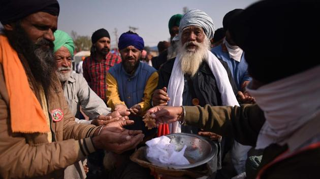 """Farmers distribute """"prasad"""" at the protest site Guru Nanak Dev Jayanti at Singhu border in New Delhi on November 30. Farmers protesting at the Tikri border and Singhu border were seen distributing prasad among each other and security personnel. (Biplov Bhuyan / HT Photo)"""