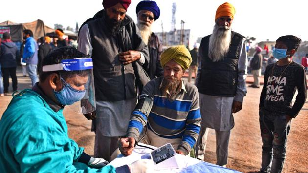 A medical professional checks on a protesting farmer at a medical camp set up near the protest site in Singhu border, New Delhi on November 30. (Biplov Bhuyan / HT Photo)