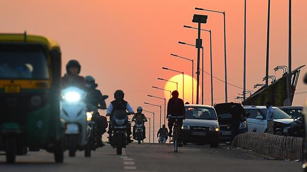 The sun sets in the background as commuters ply on NH24 in New Delhi on November 26. According to IMD officials, the minimum temperature this month, barring on November 16, has remained 2-3 degrees Celsius below normal in the absence of a cloud cover on most days. (Raj K Raj / HT Photo)