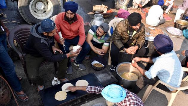 The farmers protesting against the newly enacted farm laws at Delhi-Haryana border on Monday offered prayers on the occasion of Guru Nanak Jayanti and distributed 'prasad' among each other and security personnel(ANI)