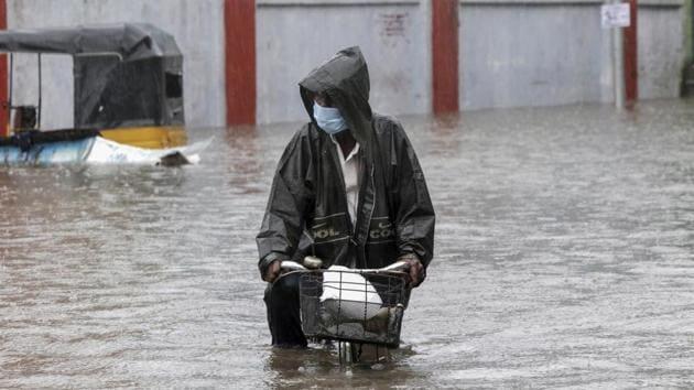 A man wearing a mask as a precaution against Covid-19 pedals his cycle through a flooded street in Chennai last week.(AP Photo)