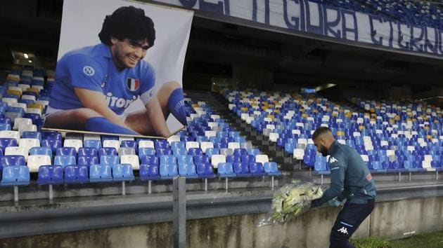 Napoli's Lorenzo Insigne lays a bouquet of flowers under a photo of Diego Armando Maradona exposed at the San Paolo stadium.(AP)