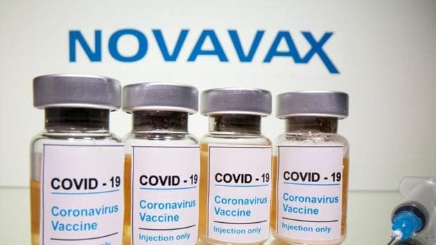 """Vials with a sticker reading, """"Covid-19 / Coronavirus vaccine / Injection only"""" and a medical syringe are seen in front of a displayed Novavax logo in this illustration.(Reuters)"""