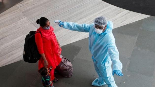 A health worker in personal protective equipment (PPE) checks the temperature of a passenger at a railway station, amid the spread of the coronavirus disease (Covid-19), in Mumbai on November 27, 2020.(Reuters File Photo)