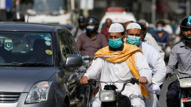Men wear protective masks as they ride a motorcycle amid the outbreak of the coronavirus disease (Covid-19) in Karachi, Pakistan.(Reuters)