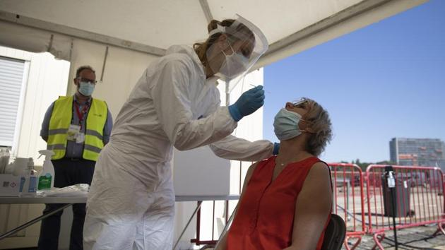FILE - In this Wednesday, Aug. 5, 2020 file photo, healthcare workers perform tests in a tent at a drive-thru Covid-19 testing site in Antwerp, Belgium.(AP)