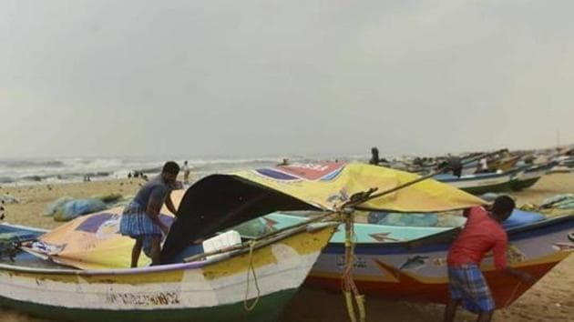 A fisherman covers his boats at Marina Beach in Chennai during heavy rains triggered by Cyclone Nivar in this file photo.(PTI)