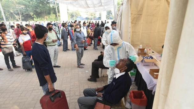 A healthcare worker collects a swab sample from a traveller at Anand Vihar ISBT, in New Delhi on Monday.(Vipin Kumar/HT Photo)