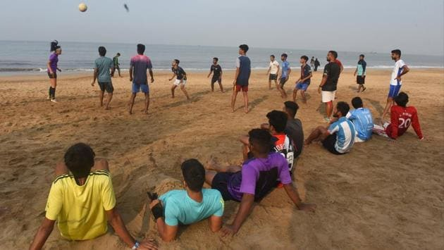 People watch a game of football being played at Juhu Beach in Mumbai on December 1. A rise in infections in the Maharshtra capital without a sharp spike, suggests the Covid-19 situation is in control post Diwali, according to Brihanmumbai Municipal Corporation (BMC) officials, HT reported. There remains however, a need to monitor it till mid-December. (Vijayanand Gupta / HT Photo)