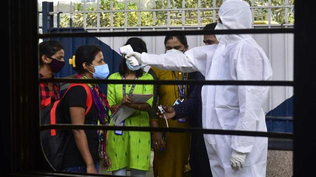 BMC medical staff thermal screening travellers arriving from Gujarat at Dadar Station in Mumbai on December 1. According to BMC health data, 3.68 lakh tests were conducted between October 1 and 28, compared to 3.48 lakh tests in the same period during November. In the same period, the case positivity rate also came down from 12% to 6%. (Anshuman Poyrekar / HT Photo)