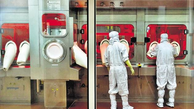 Employees operate a filling machine inside a lab at the Serum Institute of India, in Pune, on November 30.(REUTERS)