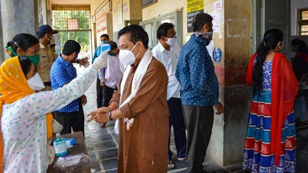A healthcare worker checks temperature of a voter as others wait in queues to cast their votes during the Graduates' and Teachers' constituency polls for Maharashtra Legislative Council, amid the Covid-19 pandemic, in Karad on Tuesday.(PTI Photo)