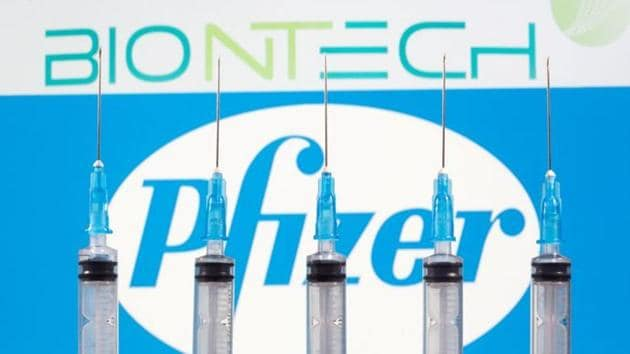 Syringes are seen in front of displayed BioNtech and Pfizer logos in this illustration.(REUTERS)