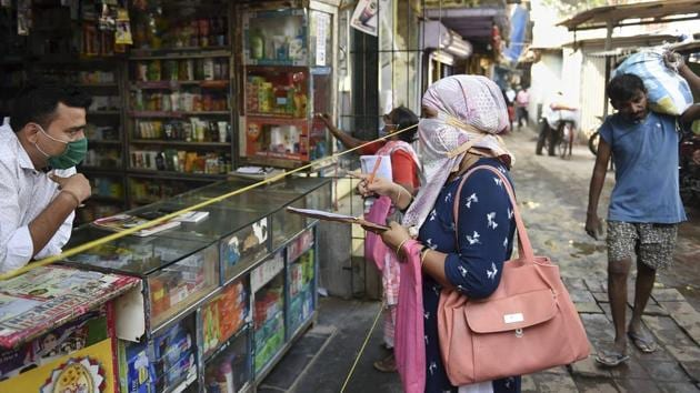 Health department workers interact with a shopkeeper during a door to door survey in Mumbai on December 1. The city has recorded a sharp decline new cases month-on-month. Between November 1 and 28, 23,476 cases were reported, compared to 46,620 cases during the same period in October. (Kunal Patil / PTI)