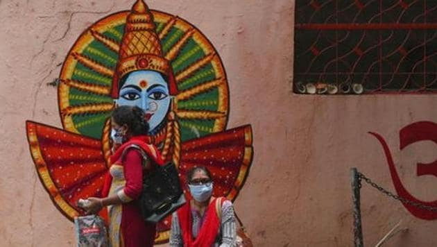 Women wearing face masks wait near a temple inside a hospital premise in Hyderabad. Andhra Pradesh is among the states that have shown a decline in the number of active Covid-19 cases.(File photo)