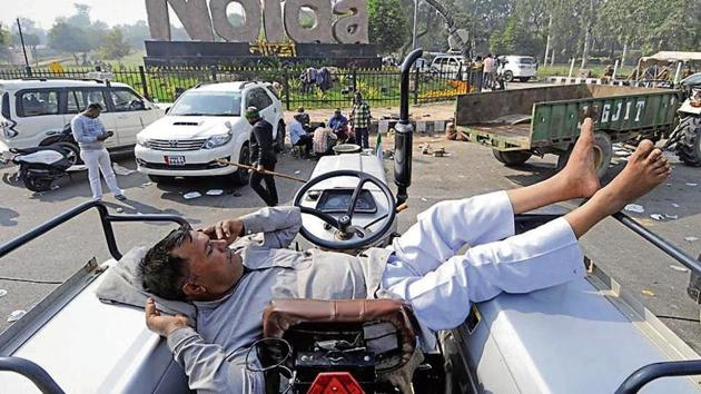 A farmer rests on his tractor at Sector 14A Noida gate on Wednesday during a protest against the new farm laws.(Sunil Ghosh/ HT photo)