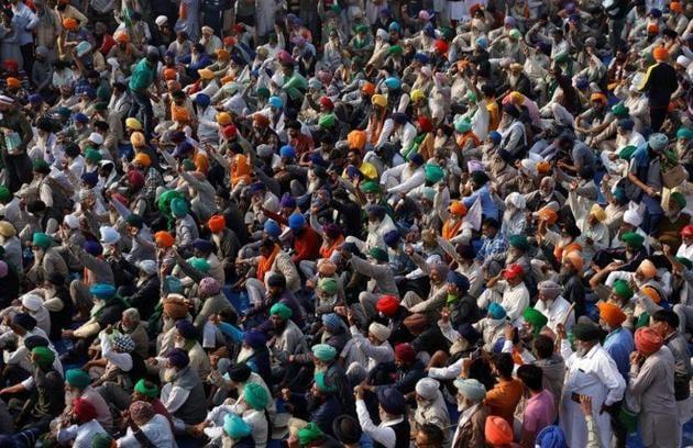 Farmers raising slogans during a protest against the new farm laws at Singhu border near Delhi on Thursday.(Reuters photo)
