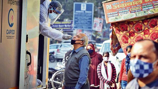 A health worker collects a swab sample for Covid-19 testing at Tilak Nagar in New Delhi on Wednesday.(Sanchit Khanna/HT photo)