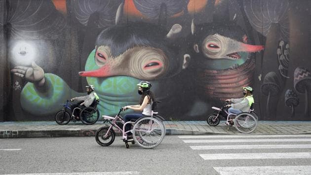 Martin Londoño, left, owner of MATT, an electric wheelchair tour company, rides with some of his clients during a tour in Medellin, Colombia, Wednesday, Nov. 18, 2020. The steering and breaks on the wheelchairs are like those on a regular bicycle, while accelerating only requires pushing a button on one of the handles.(AP)