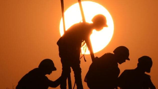 Labourers at work on a construction site against the backdrop of a setting sun on Dwarka Expressway near Sector-94, in Gurugram.(Parveen Kumar/Hindustan Times)