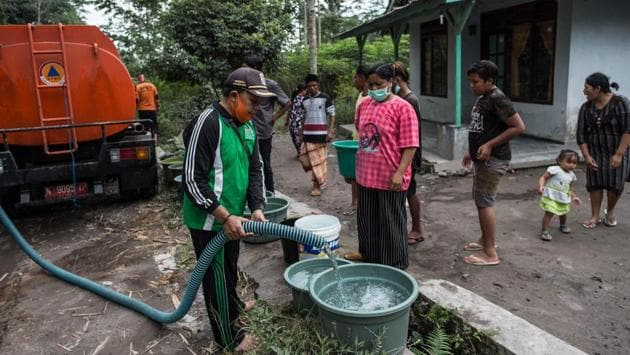 Villagers collect clean water supplied by the local government following the eruption of Mount Semeru volcano in Lumajang, East Java province, Indonesia on December 3. (Juni Kriswanto / AFP)