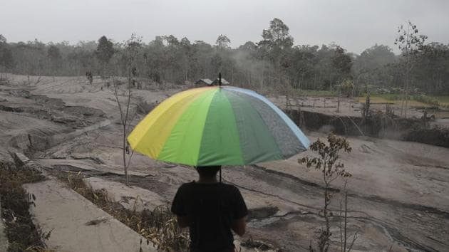 A man holds an umbrella as he looks at the damages caused by the eruption of Mount Semeru, in Lumajang, East Java, Indonesia on December 3. (Trisnadi / AP)