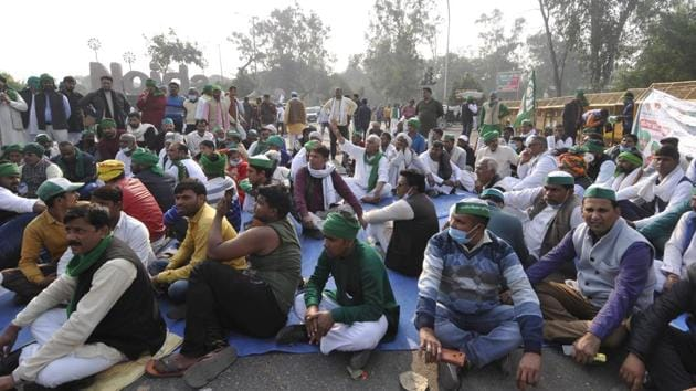 Farmers occupy the road in protest against farm reform laws at Sector 14A Noida gate in Noida on Wednesday.(Sunil Ghosh / HT)