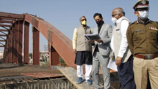 Chief minister Trivendra Singh Rawat with Mela officer Deepak Rawat, inspecting Kumbh works at a bridge site on Thursday in Haridwar.(HT Photo)
