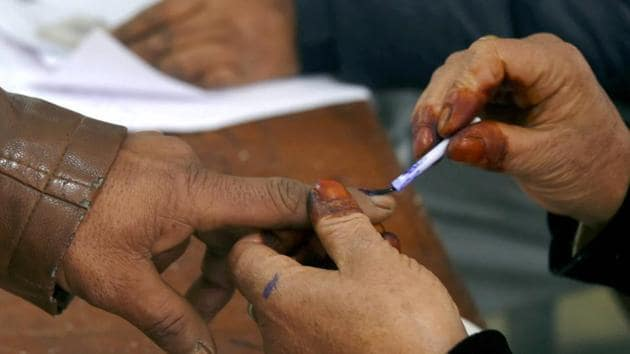A polling official inks the finger of a voter at a polling booth during the District Development Council (DDC) elections in Kashmir.(PTI)
