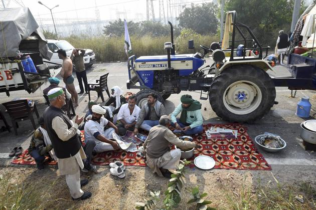 Farmers rest during a sit-in protest at Delhi-UP border over Centre's farm reform laws, in New Delhi, Friday.(PTI)