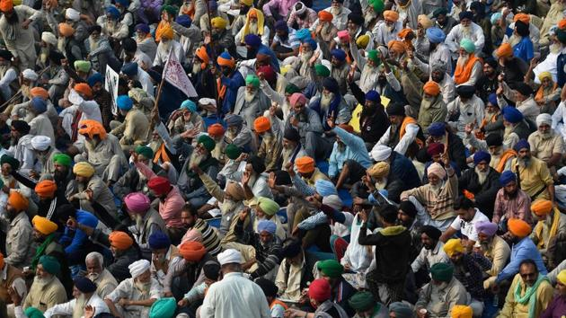 Farmers listen to a speaker as they take part in a protest against the central government's recent agricultural reforms at the Delhi-Haryana state border in Singhu on Friday.(AFP)