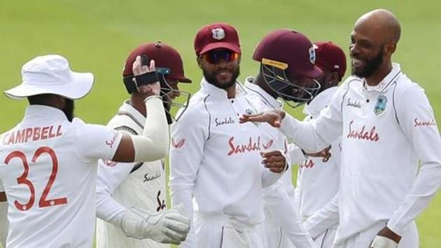 West Indies' Roston Chase celebrates taking the wicket of England's Rory Burns, caught by West Indies' Rakheem Cornwall with teammates, as play resumes behind closed doors following the outbreak of the coronavirus disease (COVID-19).(REUTERS)
