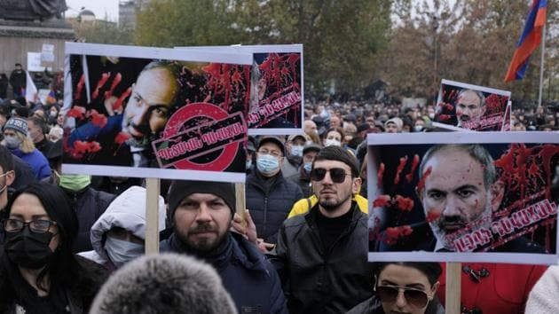 Opposition demonstrators hold posters of Armenian Prime Minister Nikol Pashinyan painted in red to represent the blood of those killed during the conflict Armenian soldiers and civilians as they attend a rally to pressure him to resign over a peace deal with neighboring Azerbaijan in Republic Square in Yerevan, Armenia, Saturday, Dec. 5, 2020.(AP photo)