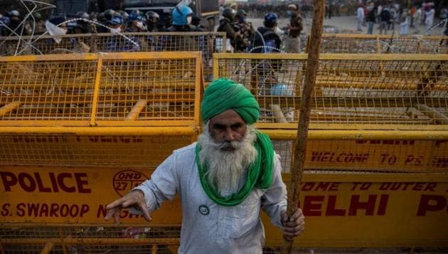 A farmer stands in front of police barricades during a protest against the newly passed farm bills at Singhu border near Delhi, India, December 3, 2020.(Reuters file photo)