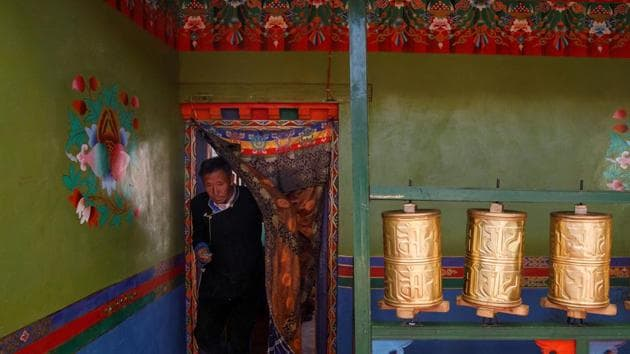 Tibetan barley farmer Dzekyid walks past prayer drums in his house during an officially organised meeting in Jangdam village in Samzhubze District outside Shigatse, Tibet Autonomous Region, China.(Reuters)