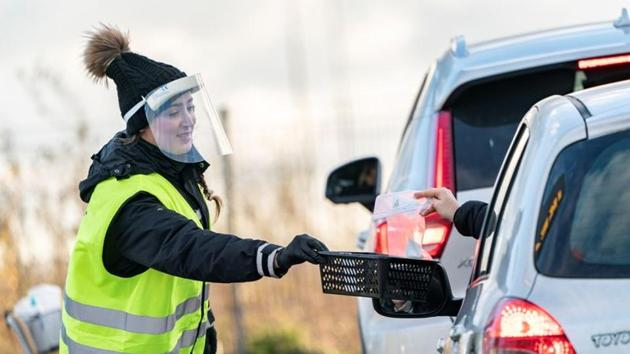 A person waring a protective mask collects coronavirus self tests from people in cars at a testing site in the car park of Svagertorp railway station, amid the coronavirus disease (Covid-19) outbreak, in Malmo, Sweden.(Reuters)
