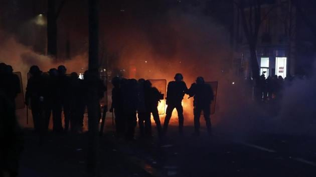Riot police officers stand in front of a fire during a demonstration in Paris.(AP)