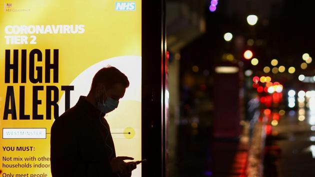 A man uses a phone at a bus stop in London.(REUTERS)